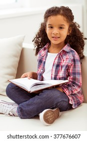 Cute little Afro-American girl in casual clothes holding a book and looking at camera while sitting on a sofa in the room.