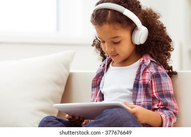 Cute little Afro-American girl in casual clothes and headphones using a tablet and listening to music while sitting on a sofa in the room.