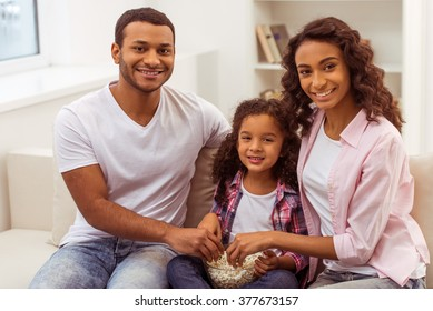 Cute little Afro-American girl and her beautiful young parents eating popcorn, looking at camera and smiling while sitting on a sofa in the room.