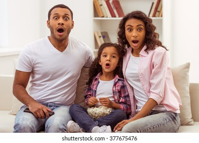 Cute little Afro-American girl and her beautiful young parents looking at camera and showing surprise while sitting on a sofa and watching TV.