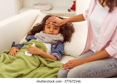 Cute little Afro-American girl with scarf on her neck is ill, lying in bed with temperature. Mother touching daughter's forehead.