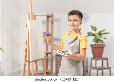 Cute little artist painting at home