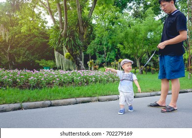 Cute little Asian 1 year old toddler baby boy child in beautiful park tethered on a leash and walking along a pavement, Dad and son cross over the road in public park, kid Strapped to a Backpack Leash