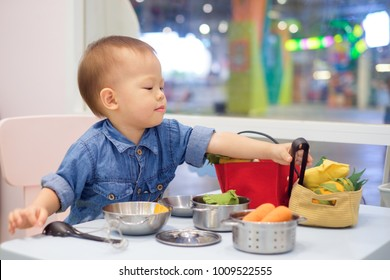 Cute little Asian 18 months / 1 year old toddler baby boy child having fun playing alone with cooking toys at play school / child care in department store, Educational toys for young children concept