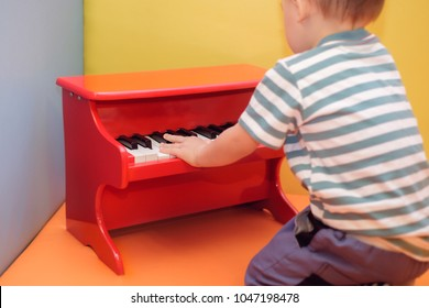 Cute little Asian 18 months / 1 year old toddler baby boy child play red piano in playroom / daycare , Musical instrument for children , Educational toys for kids concept Selective focus at kid hand
