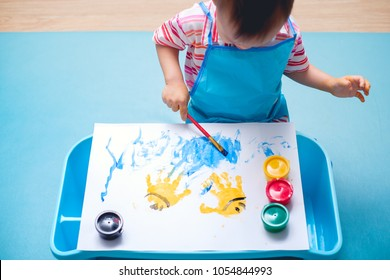 Cute little Asian 18 months / 1 year old toddler baby boy child painting with paint brush and watercolors, Early Child Development, Creative play for kids & toddlers concept