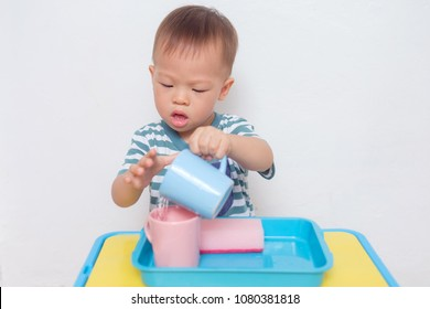 Cute little Asian 18 months old toddler boy child having fun pouring water into cup, Wet Pouring Montessori Preschool Practical Life Activities, Fine Motor Skills, Kid Sense Child Development concept