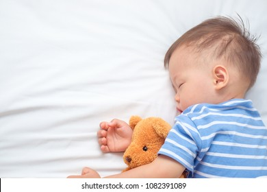 Cute little Asian 18 months / 1 year old toddler boy child sleeping / taking a nap under blanket in bed while hugging teddy bear, kid deep sleeping, sweet dream concept, Selective focus at teddy