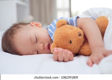 Cute little Asian 18 months / 1 year old toddler boy child sleeping / taking a nap under blanket in bed while hugging teddy bear, Daytime sleep, kid deep sleeping, sweet dream concept with copy space