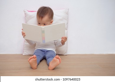 Cute little Asian 18 months / 1 year old toddler boy child sitting on floor, leaning against pillow, looking at a book near white wall, Language development, Improve concentration & focus concept