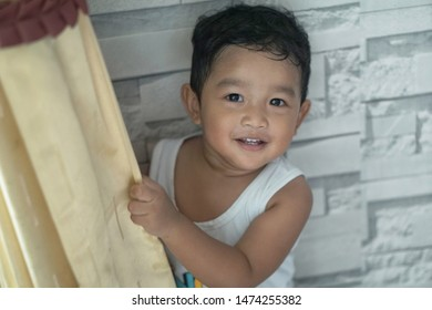Cute little Asian 18 months / 1 year old toddler baby boy child wearing white sweater is hiding in the closet at home, Funny kid play hide and seek peeking / looking out photo not focus blur concept.