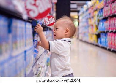 Cute little Asian 18 months / 1 year old toddler baby boy child standing and choosing milk product in grocery store / department store, kid purchasing milk in shop