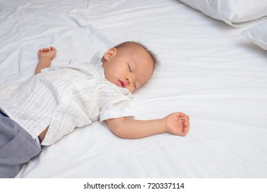Cute little Asian 18 months / 1 year old toddler baby boy child sleeping in bed in bedroom, Peaceful kid lying on bed while sleeping, Daytime sleep concept, kid deep sleeping with copy space