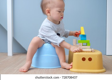 Cute little Asian 18 months old / 1 year old toddler baby boy child sitting on potty playing with wooden blocks toy. Kid playing with educational toy & Toilet training concept. - Selective focus
