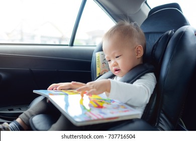 Cute little Asian 18 months / 1 year old toddler baby boy child sitting in car seat holding and enjoy reading book, Happy traveling with child concept, Little Traveler safety, road trip concept