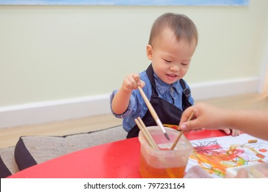 Cute little Asian 18 months / 1 year old toddler baby boy child painting with brush and watercolors at art class, kid painting with nursery teacher in a kindergarten,Creative play for toddlers concept