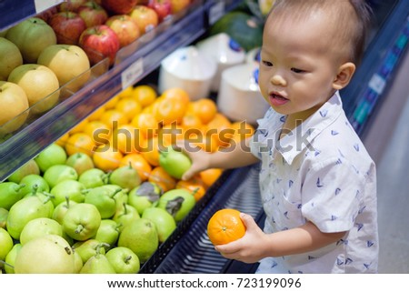 Cute little Asian 18 months / 1 year old toddler baby boy child shopping in a supermarket. Kid standing choosing and holding fruit in grocery store, Kid first experience concept - Selective focus