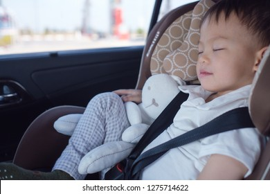 Cute little Asian 2 - 3 years toddler baby boy child sleeping in modern car seat. Child traveling safety on the road. Safe way to travel fastened seat belts in vehicle with young kid concept