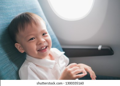Cute little Asian 2 -3 years old toddler baby boy child smiling looking at camera during flight on airplane. Flying with children, Happy air travel with kids & little traveler concept