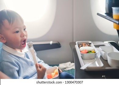 Cute little Asian 2 -3 years old toddler baby boy child wearing blue sweater eating food during flight on airplane. Flying with children, Happy air travel with kids & little traveler concept