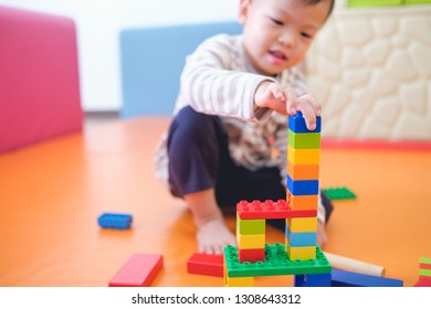 Cute little Asian 2 - 3 years old toddler boy child having fun playing with colorful plastic blocks indoor at play school / nursery / living room, Educational toys for young children concept