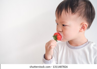 Cute little Asian 2 -3 years old toddler baby boy child using hands eating strawberry, Healthy snacks & Self feeding concept, Selective focus at kid's left eye with copy space