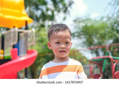Cute little Asian 2 - 3 years old toddler baby boy child sweating during having fun playing, exercising outdoor at playground on nature at park, Heat stroke and summer sunstroke risk symptom concept