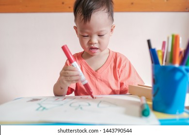 Cute little Asian 2 - 3 years old young toddler boy child drawing, scribbling with pen color marker, kid write in living room at home, Creative play for toddlers, fine motor skills development concept