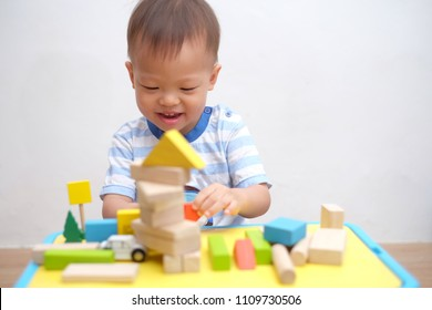 Cute little Asian 2 years old toddler boy child sitting on wooden floor having fun playing with wooden building block toys indoor at home, Educational toys for young children concept