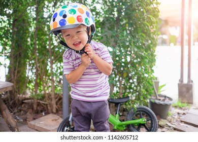 Cute little Asian 2 years old toddler boy child getting ready for cycle by wearing, fitting bicycle helmet before riding balance bike by himself, Encourage Self-Help Skill in Children, Safety concept