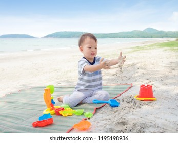 Cute little Asian 2 years old toddler boy sitting & playing children's beach toys on sandy tropical beach, Family travel, water outdoor activity on beach vacation, Sensory play with sand concept