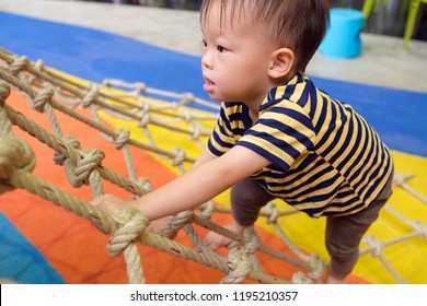 Cute little Asian 2 years old toddler baby boy child having fun trying to climb on jungle gym at indoor playground, Physical, Hand and Eye Coordination, Sensory, Motor Skills development concept