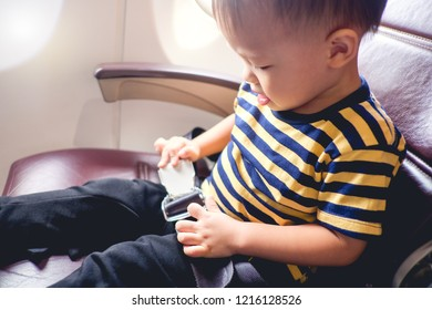 Cute little Asian 2 years old toddler baby boy child wearing striped t-shirt fasten seat belts while sitting on airplane seat. Safety measures on board. Precautions on plane during flight for kid