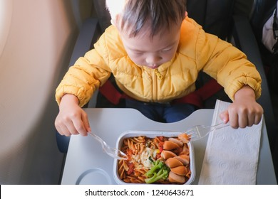 Cute little Asian 2 years old toddler baby boy child wearing yellow jacket eating food (pasta) during flight on airplane. Flying with children, Happy air travel with kids & little traveler concept