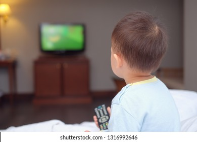 Cute little Asian 2-3 years old toddler baby boy child sitting in bed holding the tv remote control and watching television in bedroom at home, Toddlers Screen Time & Early Brain Development concept