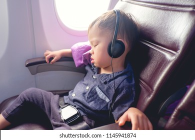 Cute little Asian 24 months / 2 years old toddler baby boy child sleeping on Airplane, Toddler boy sitting with safety belt on wearing headphones while traveling in airplane, Kids Fly Safe concept