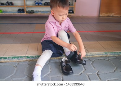 Cute Little Asian 3 - 4 years old kindergarten kid in uniform sitting and concentrate on putting on children's classics boys black leather velcro Shoes, Encourage Self-Help Skills in Children concept