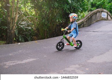Cute little Asian 3 - 4 years old toddler boy child wearing safety helmet learning to ride first balance bike down a hill in sunny day, kid playing & cycling at park, Cycling with young kids concept