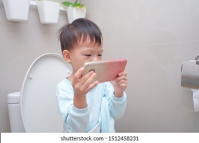 Cute little Asian 3 - 4 years old toddler boy kid using mobile phone while sitting on toilet seat in bathroom at home, Screentime & Potty Training & young children concept, photo in real life interior