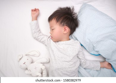 Cute little Asian 3 - 4 years old toddler boy kid in pajama sleeping / taking a nap on white bed sheet in bed , Bedtime for kids concept with copy space