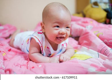 Cute little Asian 3 months old toddler baby boy child on blanket in bedroom at home. Newborn child relaxing. Nursery for young children. Soft and Selective focus