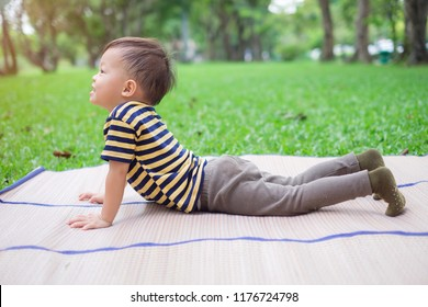 Cute little Asian 30 months / 2 year old toddler baby boy child practices yoga in Cobra Pose and meditating outdoors on nature in summer time, Healthy lifestyle, Yoga for Kids to improve concentration