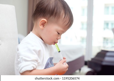 Cute little Asian 30 months / 2 years old toddler baby boy child who having flu feeding himself with liquid medicine with a syringe, Fever cold and flu concepts. Selective focus at medicine & syringe