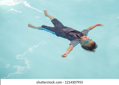 Cute little Asian 30 months / 2 years old toddler baby boy learn to swim in swimming class in Thailand, Kid learn to float (back floating) at indoor salt water pool, Beginner Swimmers concept