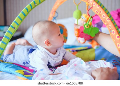 Cute little Asian 5 - 6 months old  baby boy child at tummy time on the play gym playing with his Daddy on Bed in Bedroom at Home - Selective Focus