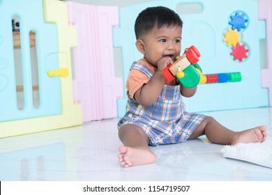 cute little asian baby boy bite wooden toy
