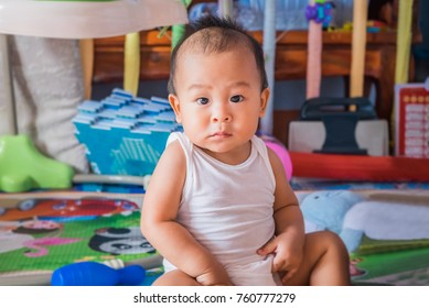 Cute little asian baby boy relaxing and looking up camera in the crib at home. Nursery for young children. Breastfeeding or early childhood development concept