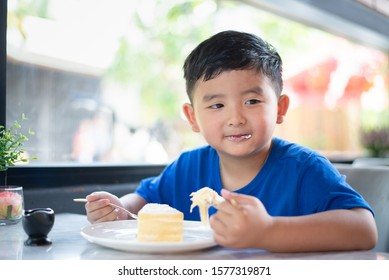 Cute little Asian boy eating cake in bakery shop or cafe.