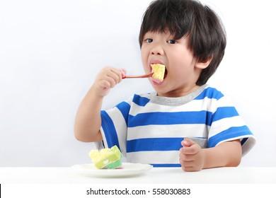 Cute little Asian boy enjoying cake, sweet food.