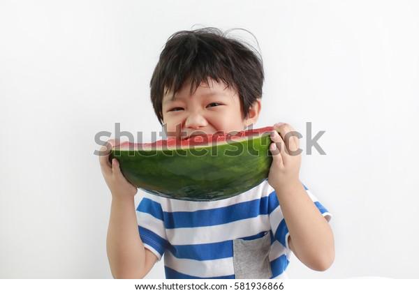 Cute little Asian boy enjoying watermelon isolated on white background